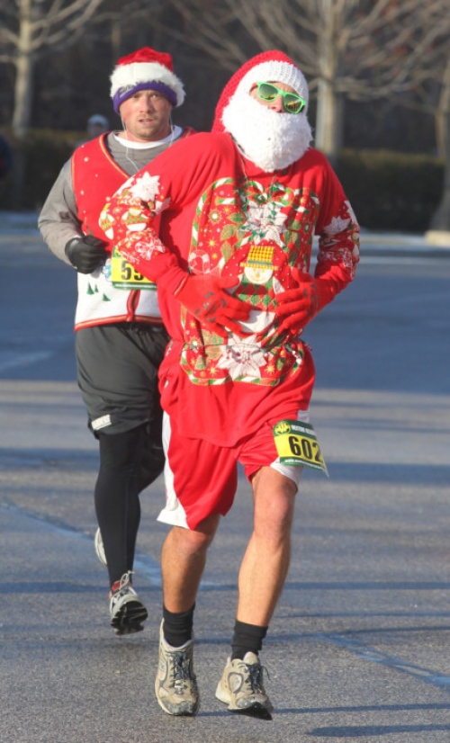man running as Santa holding belly